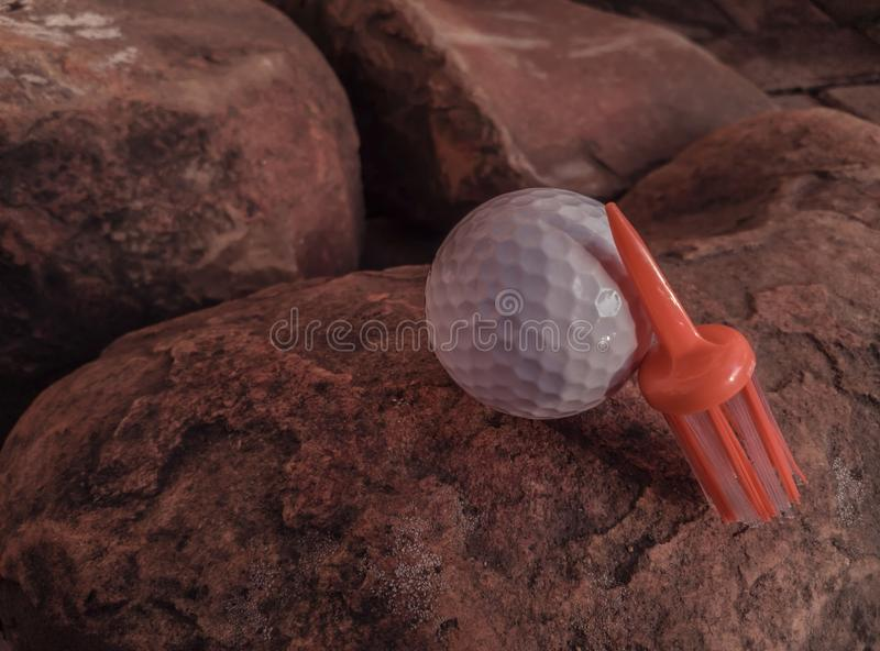 White Ball With Orange Brush Tee Placed On Rocky Surface royalty free stock photos