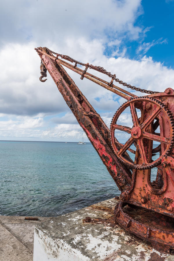Angled view of Antique red iron boat crane anchored in concrete stock photo
