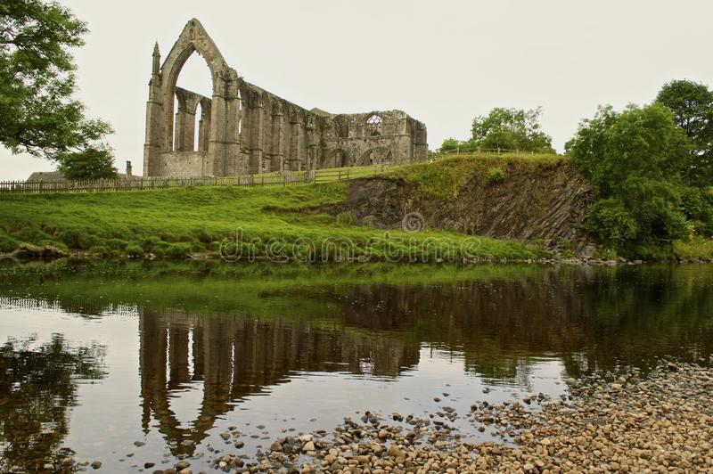 Angled view of Bolton Priory. The ruins of the 12th century Augustinian monastery known as Bolton Priory, reflected in the river Wharfe. Situated in the estate stock photo