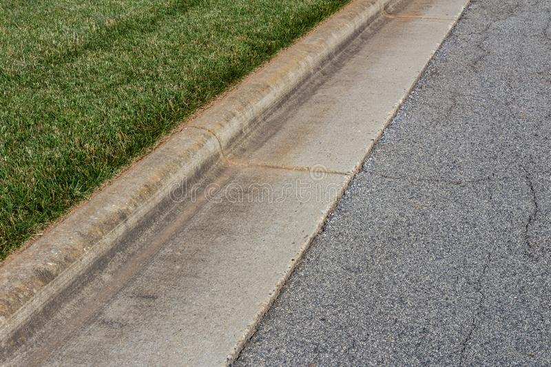 Angled view formed concrete curb, green grass and asphalt street. Horizontal aspect royalty free stock image