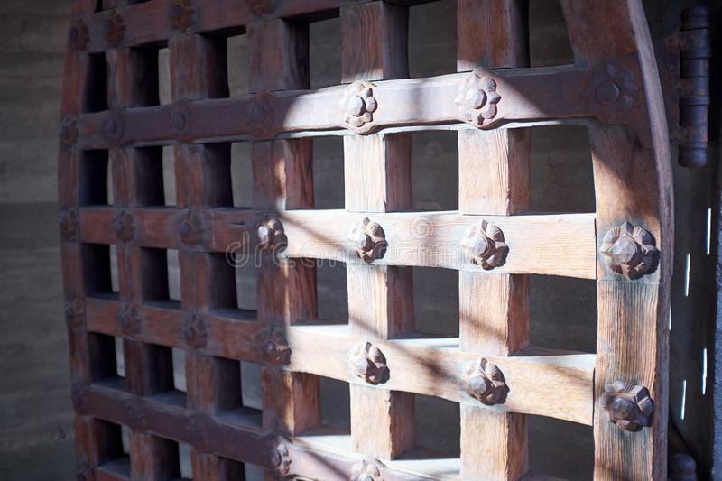 Angled view of a half shaded metal portcullis arched door with a flower pattern that is partially opened up at Death Valley National Park & Angled View Of Patterned Metal Portcullis Door Stock Photo - Image ...