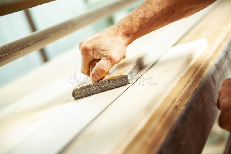 Angled view of man using wood sander with handle royalty free stock photography