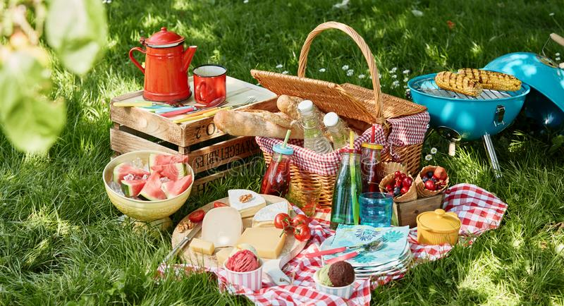 Angled view of picnic blanket and basket. Next to small blue barbecue and wooden box sitting in green field with dappled sunlight and blurry leaf in foreground royalty free stock image