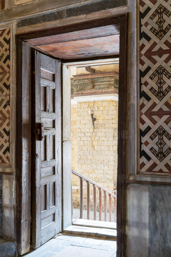 Wooden aged ornate opened door leading to a passage with bright light, color decorated marble wall, and marble floor royalty free stock photos