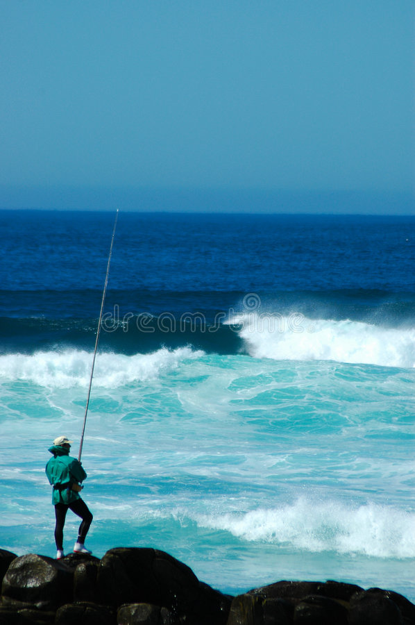 Angler. An angler fishing in the Indian Ocean during high tide at Schoenmakerskop Beach, Port Elizabeth, South Africa stock photos