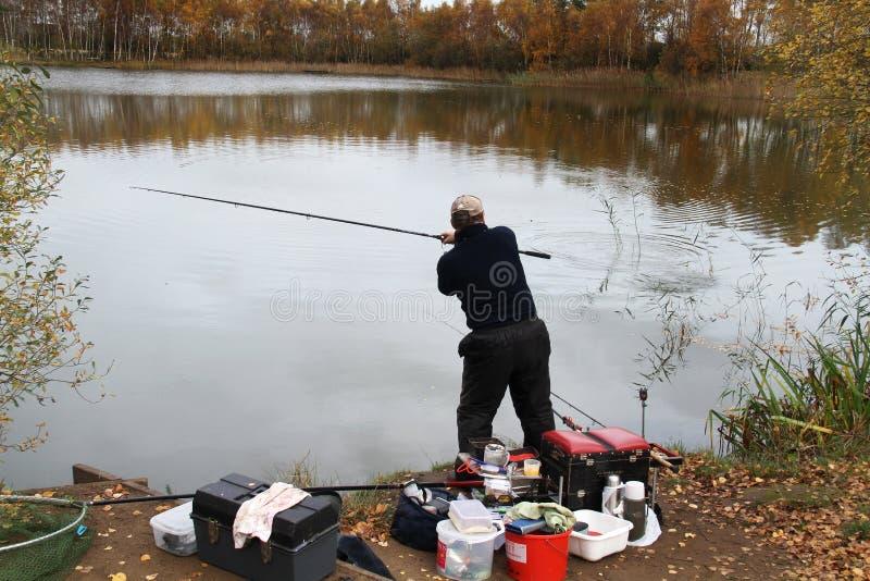 Angler che gioca a carpa grande in posizione di atterraggio fotografie stock libere da diritti