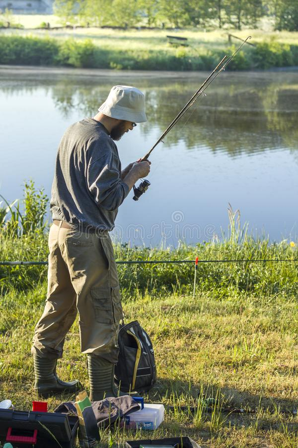 Angler in a hat and wellingtons is standing over the water with a fishing rod. stock photo