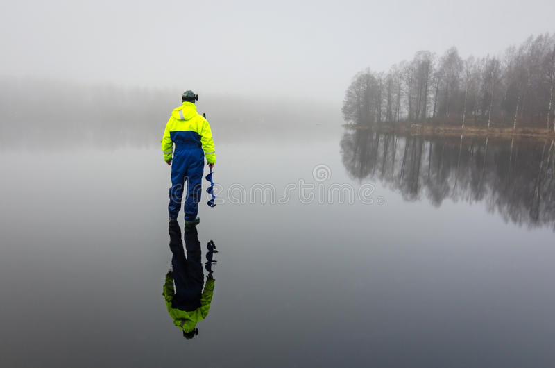 Angler with ice drill. Angler on the lake ice in foggy day stock photography