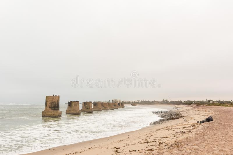 Angler and old railroad bridge over the mouth Swakop River. SWAKOPMUND, NAMIBIA - JUNE 30, 2017: An angler and pillars of the old railroad bridge over the mouth stock photo