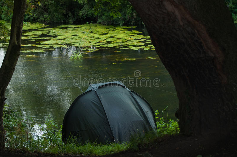 Angler in shelter waiting for a bite royalty free stock photo