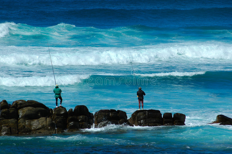 Anglers. Two active anglers fishing in the Indian Ocean during high tide at Schoenmakerskop Beach, Port Elizabeth, South Africa