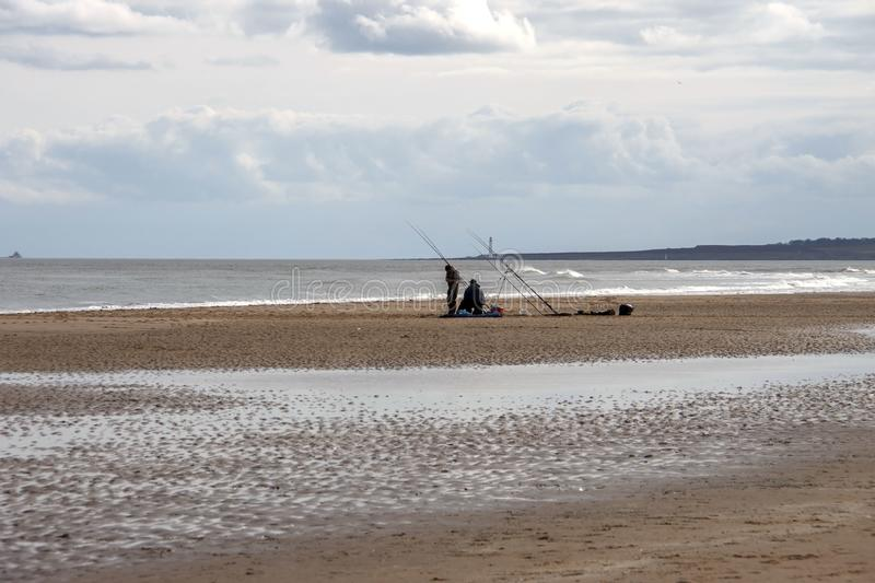 Anglers fishing by the sea. St Cyrus, Aberdeenshire, Scotland royalty free stock photo