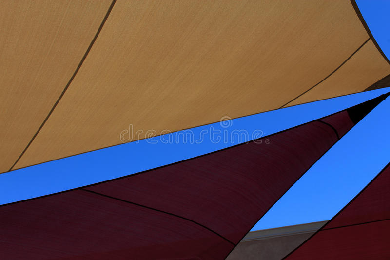Angles. These tarp covers against the deep blue sky made for interesting angles of lines and colors. Gold tarp with brown trim. Maroon tarp with black trim. Tan royalty free stock image