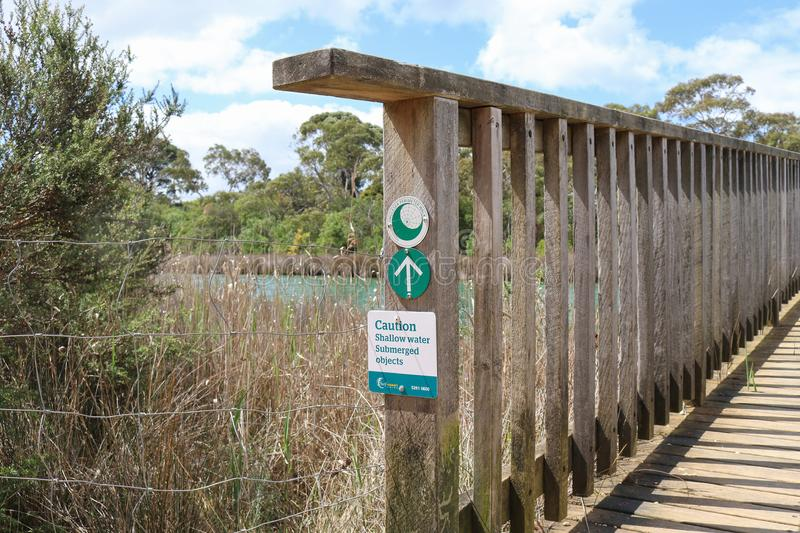 A green and white Shallow Water Submerged Objects warning sign. ANGLESEA, AUSTRALIA - October 9, 2017 - a green and white Shallow Water Submerged Objects warning stock images