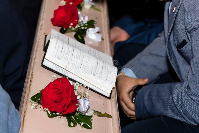 Anglican hymnu książkowe i czerwone róże w kościół obraz stock