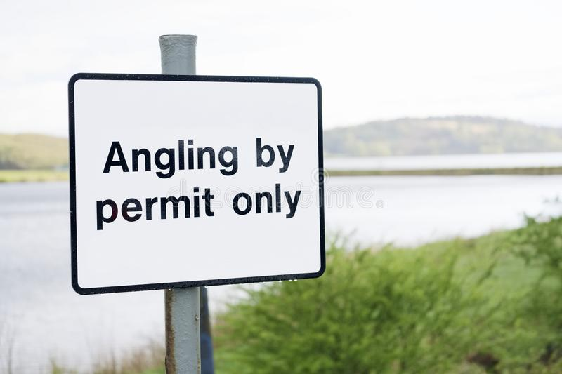 Angling by permit only sign at freshwater lake. Uk royalty free stock photography