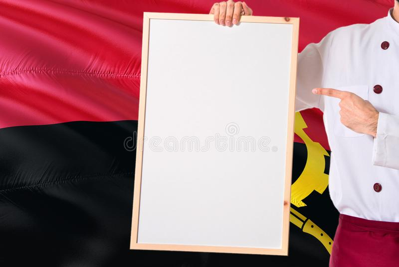 Angolese Chef-kok die leeg whiteboardmenu op de vlagachtergrond van Angola houdt Kok die eenvormige richtende ruimte voor tekst d stock afbeelding