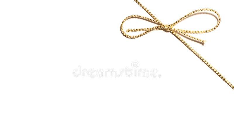 Angolo in alto a destra della corda dorata del raso con l'involucro annodato del nastro del regalo dell'arco per regalo di Natale immagine stock