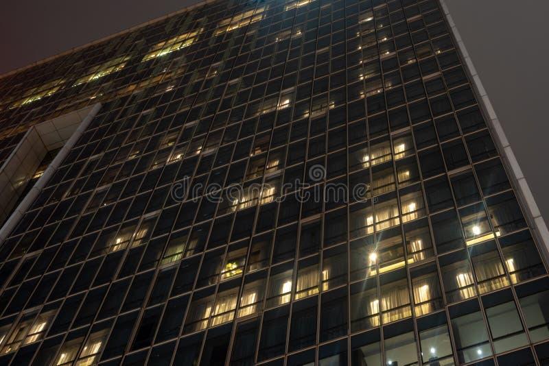 Angolo basso di costruzione con l'esterno di vetro sul fondo del cielo notturno immagini stock