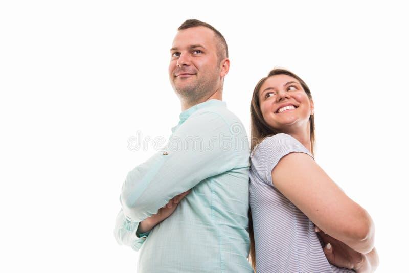 Angolo basso di giovani coppie felici che stanno di nuovo alla parte posteriore fotografia stock libera da diritti
