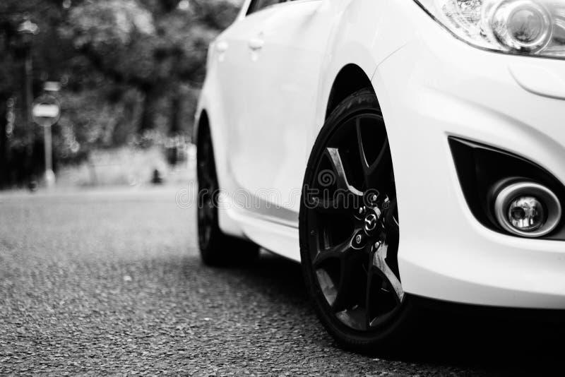 Angolo basso in scala di grigi di una Mazda bianca che guida per la strada di Wolverhampton City nel Regno Unito immagini stock