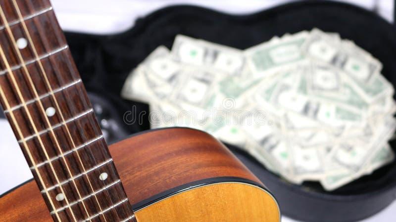 Angolo della chitarra acustica e collo su a fuoco vicino, soldi nel caso sfuocato, forte profondità di campo immagine stock