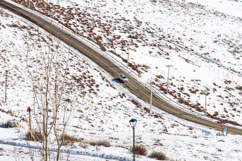 Angolo elevato di guida di un'auto su una strada circondata da campi di neve nelle Andes Cordillera, Cile fotografia stock
