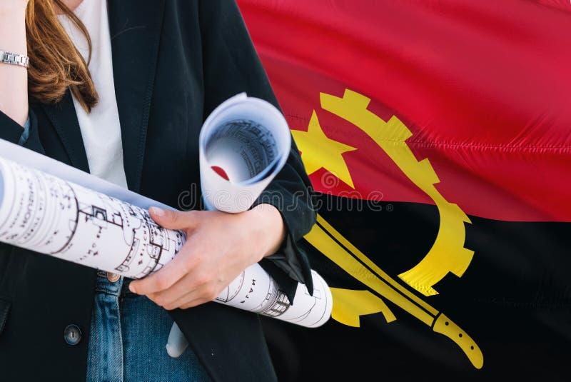 Angolski architekt kobiety mienia projekt przeciw Angola falowania flagi tłu Budowy i architektury poj?cie fotografia stock