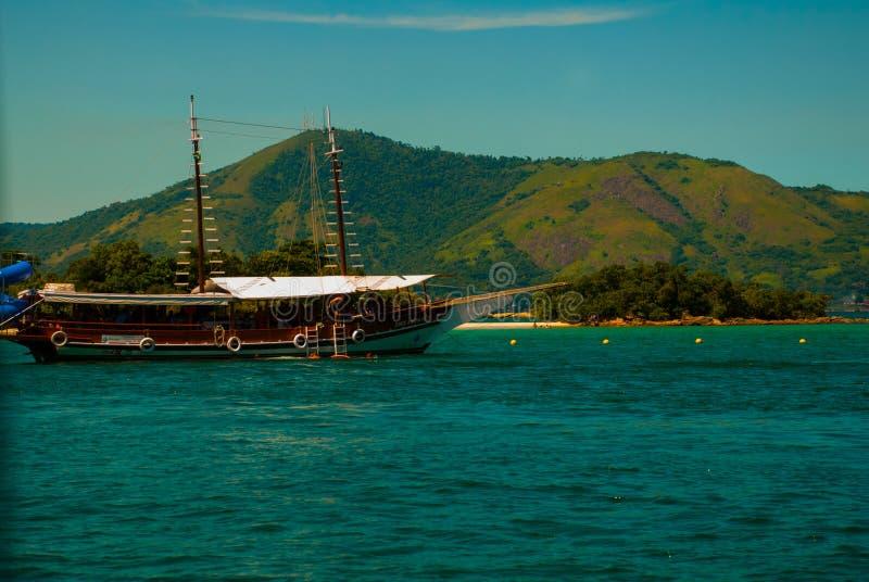 Angra DOS Reis, Brasilien, stora Ilha: Härligt landskap med skepp som förbiser havet och bergen royaltyfri foto
