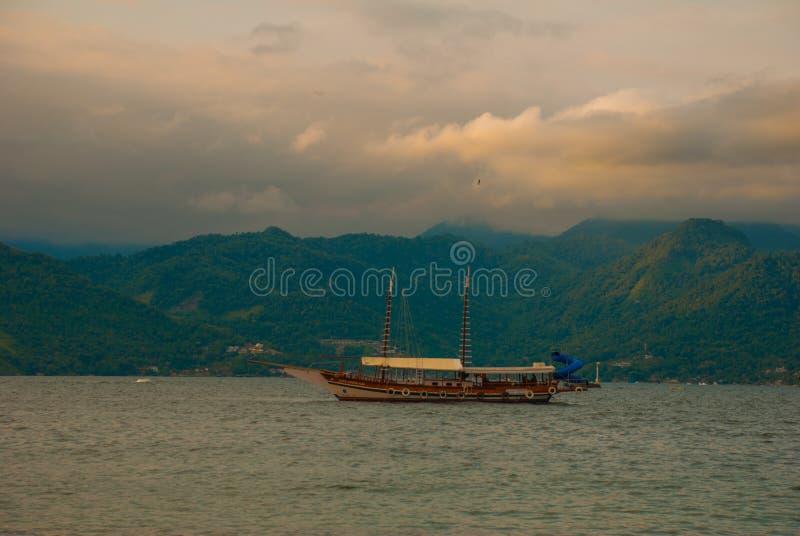 Angra DOS Reis, Brasilien, stora Ilha: Härligt landskap med skepp som förbiser havet och bergen arkivfoto