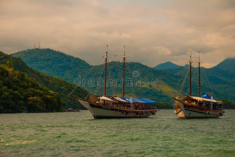 Angra DOS Reis, Brasilien, stora Ilha: Härligt landskap med skepp som förbiser havet och bergen fotografering för bildbyråer