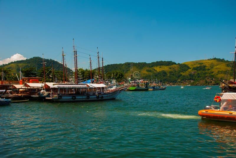 Angra DOS Reis, Rio de Janeiro State, Brasilien: Santa Luzia Pier i Angra DOS Reis Skepp med turister nära terminalen royaltyfria bilder