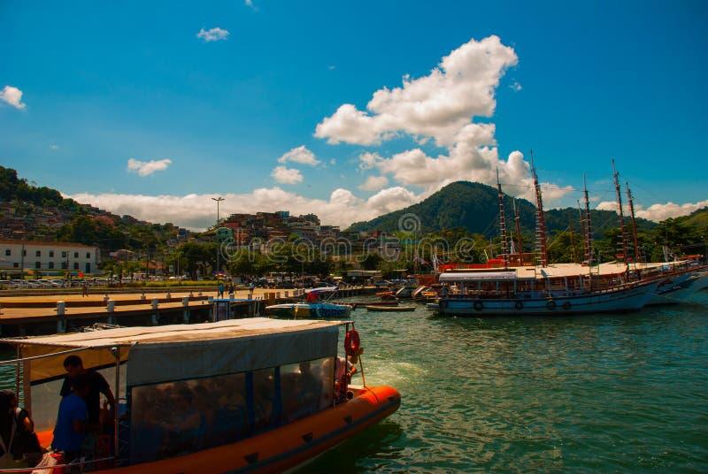 Angra DOS Reis, Rio de Janeiro State, Brasilien: Santa Luzia Pier i Angra DOS Reis Skepp med turister nära terminalen royaltyfria foton