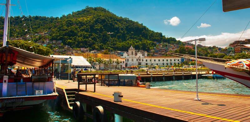 Angra DOS Reis, Rio de Janeiro State, Brasilien: Santa Luzia Pier i Angra DOS Reis Skepp med turister nära terminalen royaltyfri foto