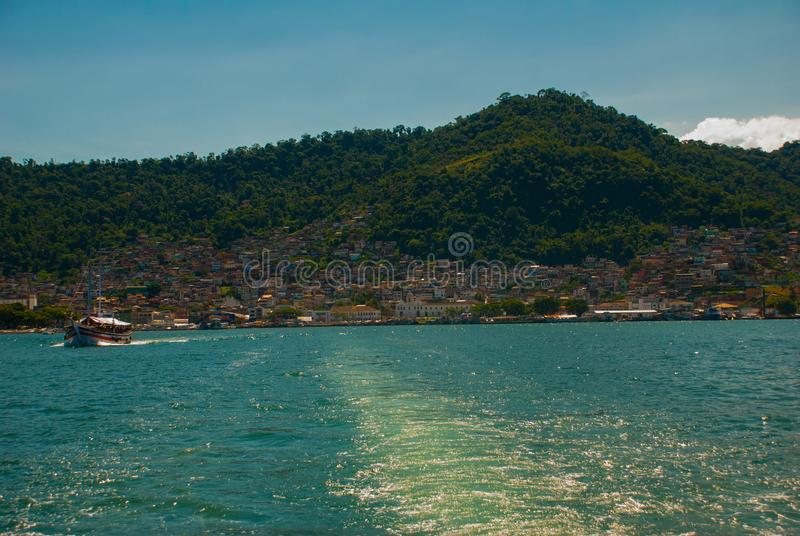 Angra DOS Reis, Rio de Janeiro State, Brasilien: Santa Luzia Pier i Angra DOS Reis Skepp med turister nära terminalen royaltyfri bild