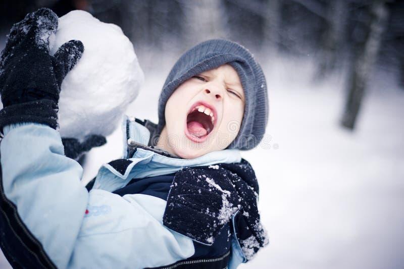 Angreifender Junge mit Schneeball stockfotos