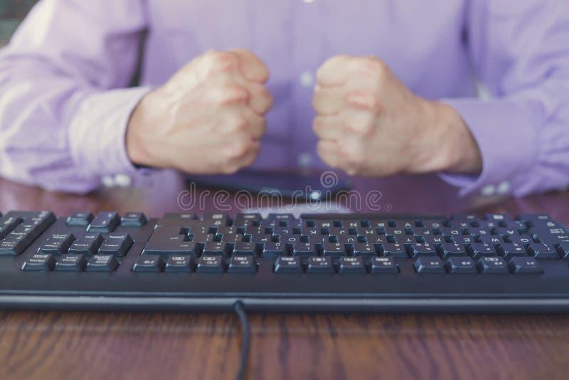 Angriff im Internet, Mann, der hinter Tastatur mit den Handfäusten zusammengepreßt sitzt lizenzfreie stockfotografie