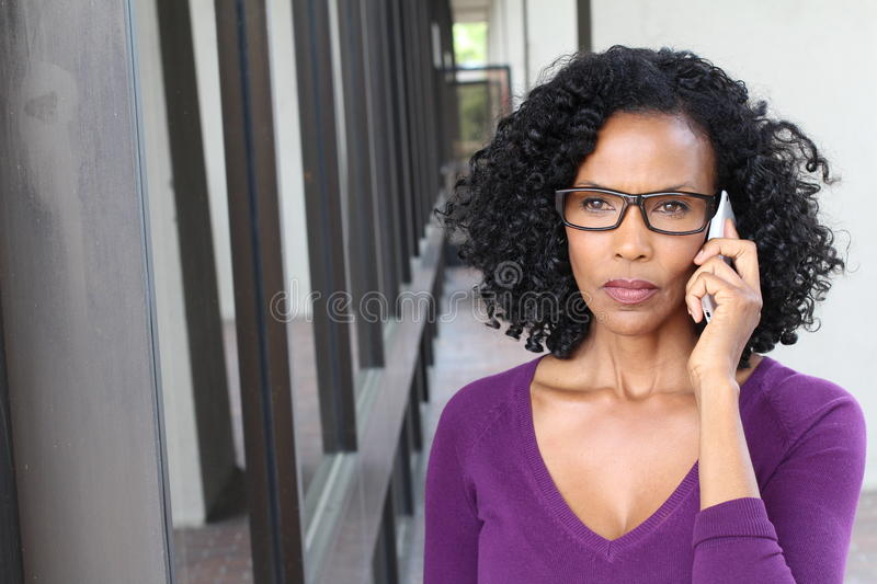 Angry African American business woman talking on cell phone. Isolated on office building with copy space royalty free stock image