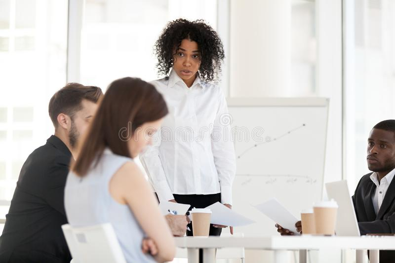 Angry African American businesswoman scolding employee for bad work royalty free stock image