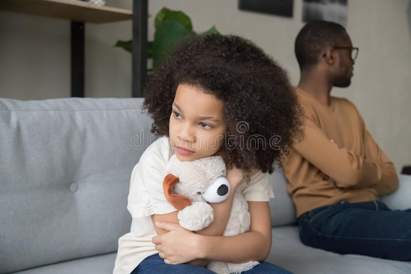Angry African American father and stubborn preschool daughter after quarrel. Angry African American father and stubborn preschool daughter with plush toy sitting stock image
