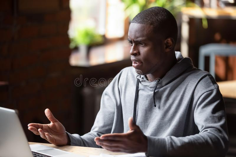 Angry African American man looking at laptop, receiving bad news stock photos