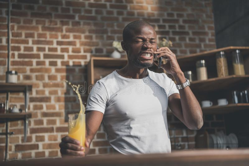 Angry african american man shed juice during tense. Phone conversation royalty free stock image