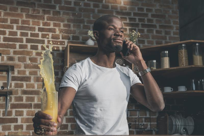 Angry african american man shed juice during tense. Phone conversation royalty free stock images