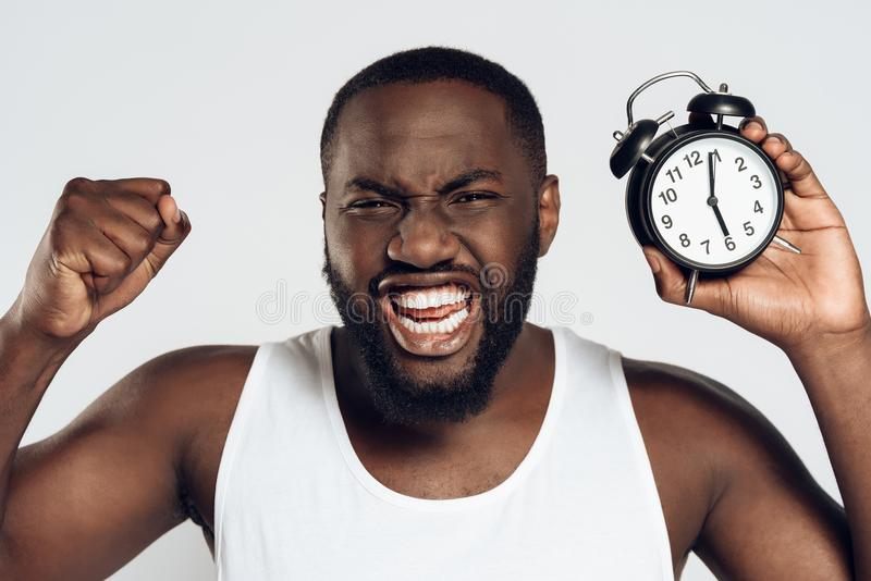 Angry African American man yells holding alarm stock photography