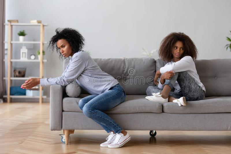 Angry African American mother and daughter not talking after quarrel stock image