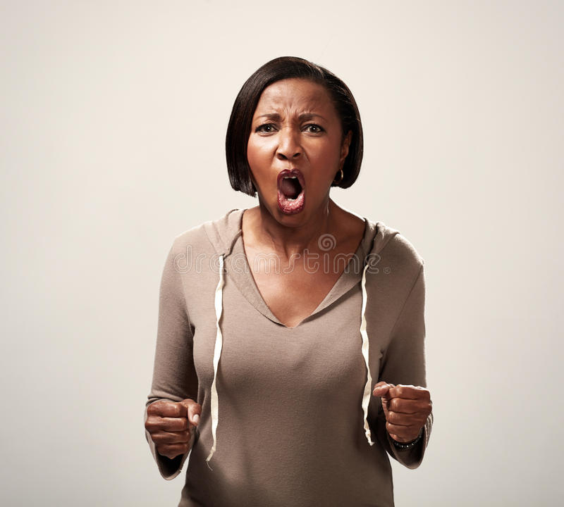 Angry african american woman. Fury irate screaming african american woman over dark background stock image