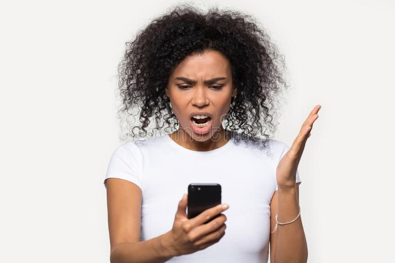 Angry African American woman looking at phone, annoyed by spam stock image
