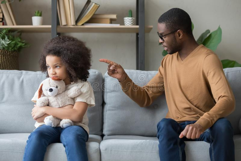African dad scolding for discipline stubborn daughter sitting on sofa. Angry african father sitting with little stubborn daughter holds stuffed toy feels upset royalty free stock photo