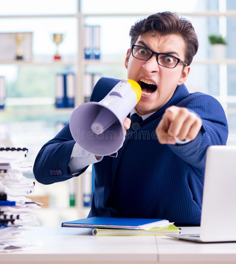 Angry aggressive businessman with bullhorn loudspeaker in office. The angry aggressive businessman with bullhorn loudspeaker in office stock photos