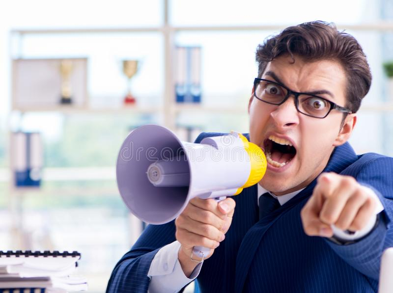 Angry aggressive businessman with bullhorn loudspeaker in office. The angry aggressive businessman with bullhorn loudspeaker in office royalty free stock photo
